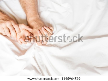 Couple having sex. Hand clutches grasps a white crumpled bed sheet in a hotel room, a sign of ecstasy, feeling of pleasure or orgasm #1145964599