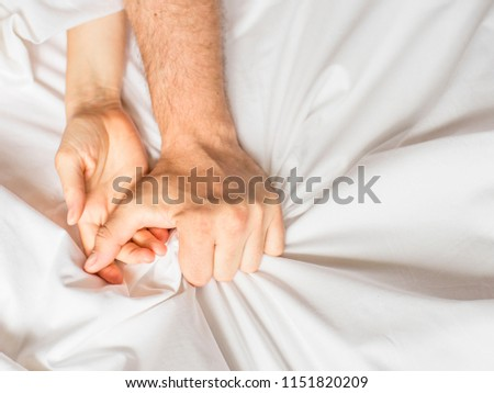 Couple having sex. Hand clutches grasps a white crumpled bed sheet in a hotel room, a sign of ecstasy, feeling of pleasure or orgasm #1151820209