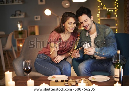 Couple having sushi meal and using cell phone
