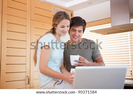 Couple having tea while using a notebook in their kitchen