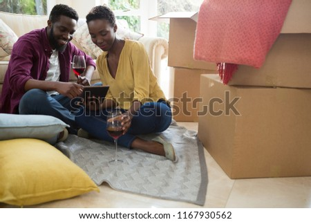 Couple having wine while using digital tablet in new house