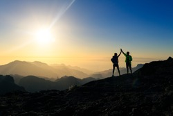Couple hikers celebrating success in sunset mountains, accomplish with arms up outstretched. Young man and woman looking at beautiful inspirational landscape view, Gran Canaria Canary Islands.