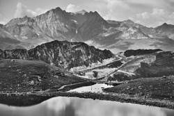 Couple hiking between lakes at French Alps near Arcs 2000 ski station. Summer in Savoie, France. Black white photo.