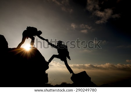 Couple hiking help each other silhouette in mountains