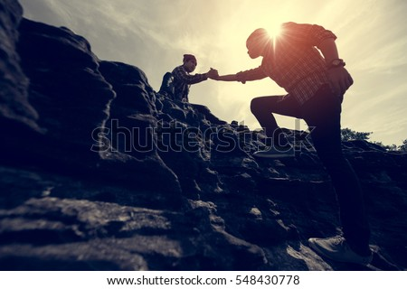 Couple hiking help each other silhouette in mountains with sunlight #548430778