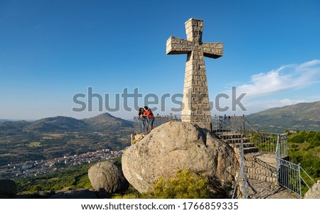 Couple hiking in the mountains at a tourist spot looking at the views on a large rock with a large cross