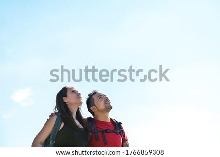 Couple hiking in the mountains looking at the sky