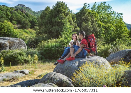 Couple hiking in the mountains resting and drinking water