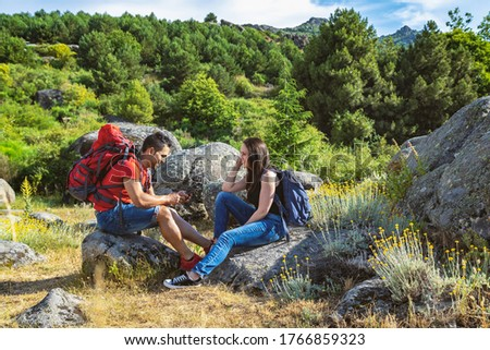 Couple hiking in the mountains sitting resting and the guy looking at the mobile phone
