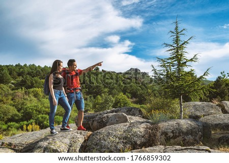 Couple hiking in the mountains, the boy points a place