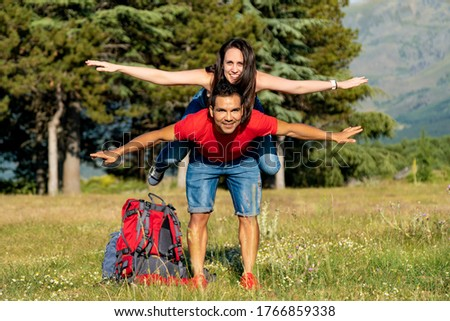 Couple hiking in the mountains the boy takes the girl on his back and opens his arms