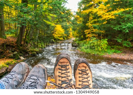 Couple hiking, muddly hiking boots over forest stream in fall #1304949058