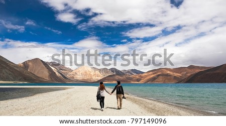 Couple hold hand together , Very nice sky and mountain , at Pangong lake , Ladakh , India