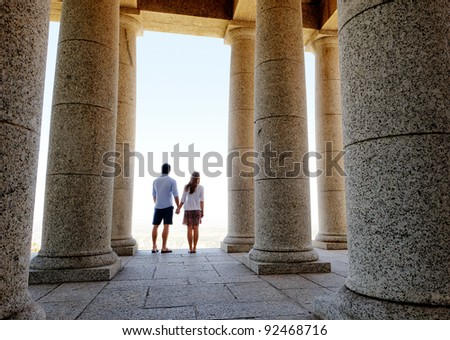 Couple hold hands at a memorial with big stone pillars, looking out into the distance - stock photo
