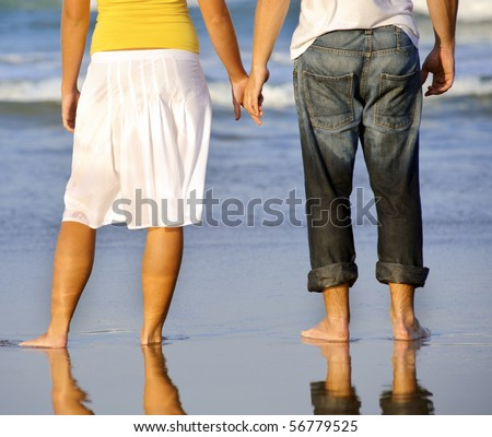 couple hold hands together while at the beach