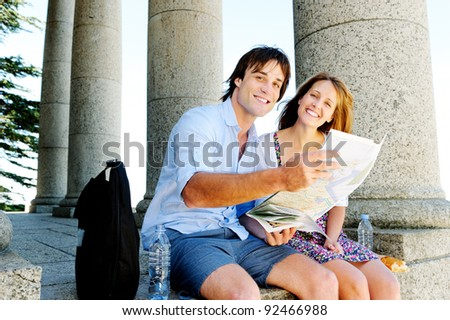 couple hold map and smile towards camera while sitting at an old tourist attraction. young travel concept