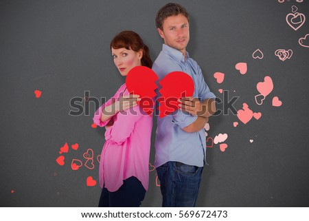 Couple holding a broken heart against grey #569672473
