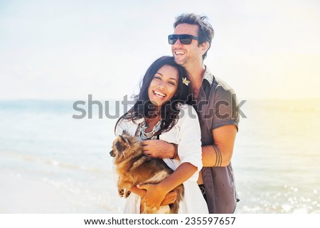 couple holding a puppy on a beach