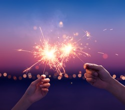 Couple holding a sparklers on the beach