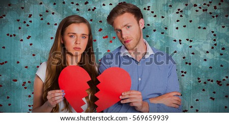 Couple holding broken heart against blue paint splashed surface #569659939