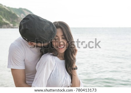 Couple holding each other on beach. Young happy interracial couple on beach holding each other. Asian woman, Caucasian man. Young mixed race romance concept. #780413173