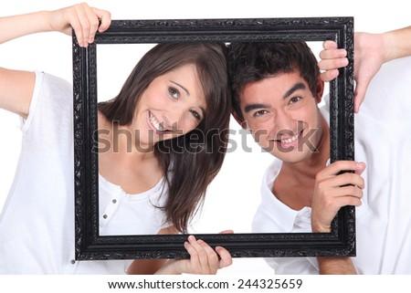 Couple holding empty frame