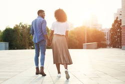Couple holding hands and walking in the city at sunset