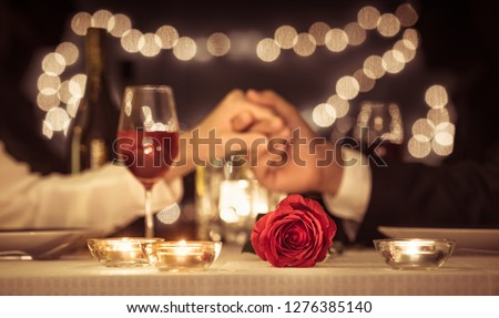 Photo of  Couple holding hands having a romantic dinner date, Valentines day, anniversary concepts.