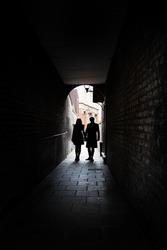 Couple holding hands in dark London alley street grimey