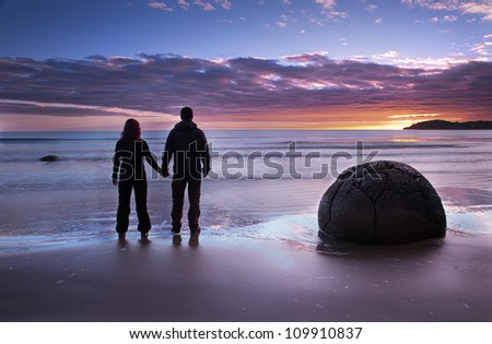 Couple holding hands looking at the sunrise at Moeraki Boulders