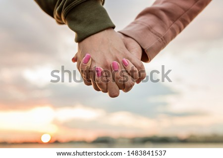 Couple holding hands outdoor on sunset. Love, family, lovestory, wedding concept