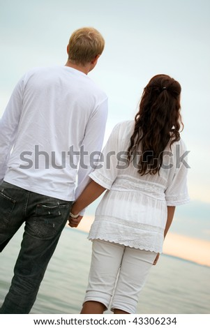 couple holding hands in sunset. stock photo : couple holding hands watching the sunset