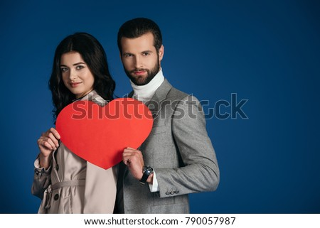 couple holding heart shaped piece of paper isolated on blue #790057987