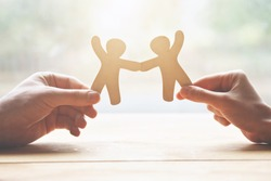 couple holding in hands wooden toy men as symbol of love and friendship