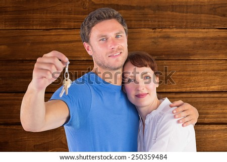 Couple holding keys to home against overhead of wooden planks
