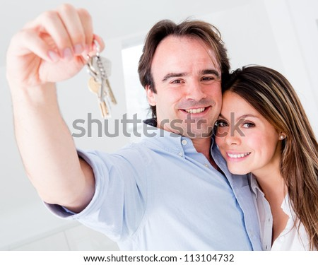 Couple holding keys to their house and looking very happy