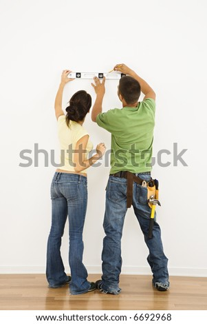 Couple holding level to interior wall and marking with pencil.