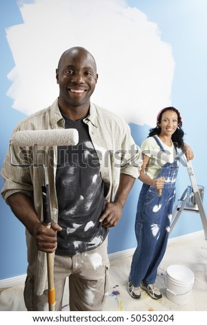 Couple holding paint rollers, portrait, elevated view