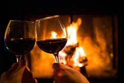 Couple holding pair of glasses with wine at fire pit close up