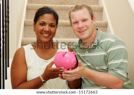 Couple Holding Piggy Bank With Their Savings