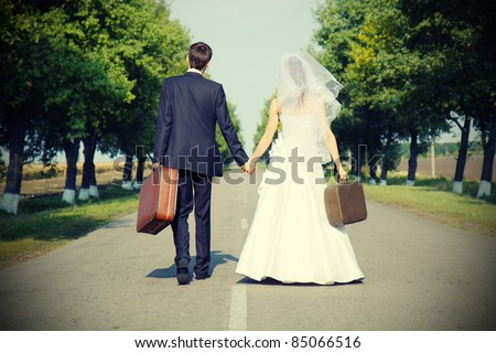 couple holding suitcases  on countryside road