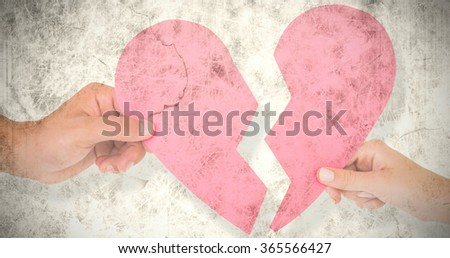 Couple holding two halves of broken heart against grey background #365566427