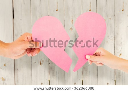 Couple holding two halves of broken heart against wooden background