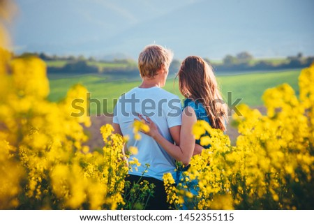 Couple hugging at sunset in yellow spring field. Romantic photo, white edit space #1452355115