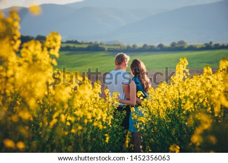 Couple hugging at sunset in yellow spring field. Romantic photo, white edit space #1452356063