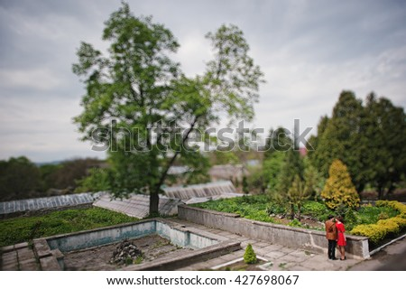 Couple hugging in love at park garden. Stylish man at velvet jacket and girl in red dress in love together. Tilt shift effect - stock photo