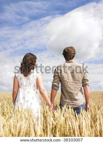Couple hugging in the middle of a wheat field