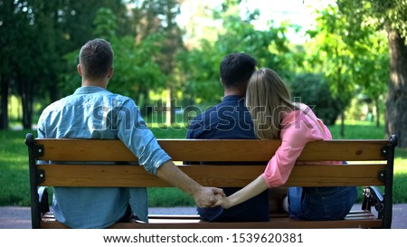 Couple hugging on bench, woman secretly holding hand of other man, betrayal Foto d'archivio ©