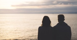 Couple hugging on the beach on background ocean sunrise, silhouette two romantic people cuddling and looking on rear view evening seascape, hipster enjoy  sunset together, travel holidays vacation