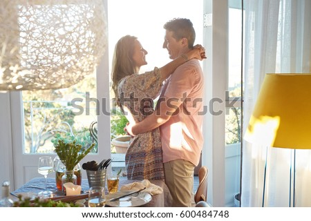 Couple hugging sharing a moment before their guests arrives for a dinner party #600484748